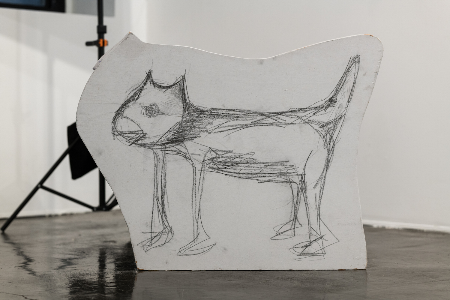 Charcoal drawing of an angry dog, applied on a wooden sculpture of a cartoon dog shape.