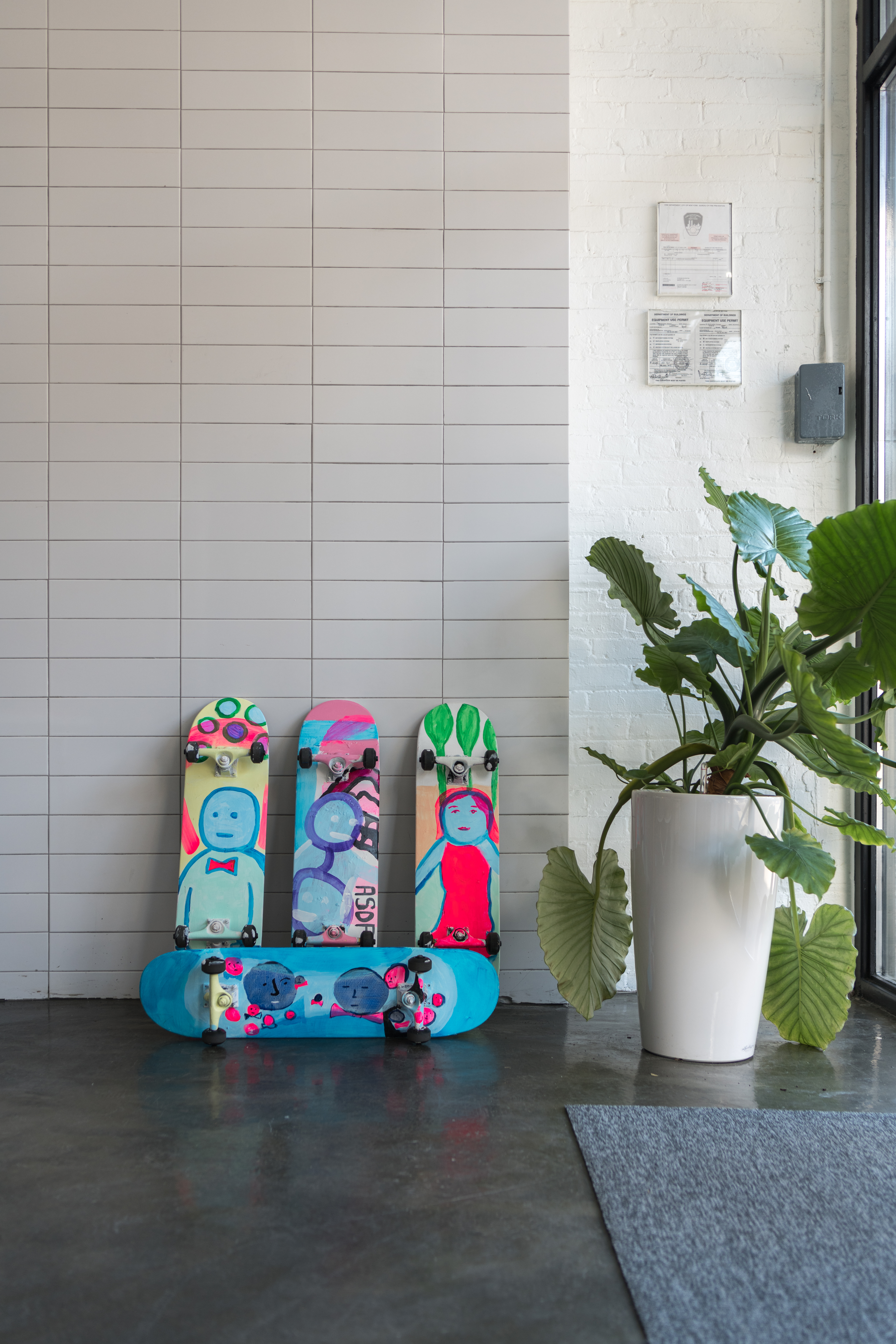 Skateboard paintings set in Recess. White tiled walls and big green tree.
